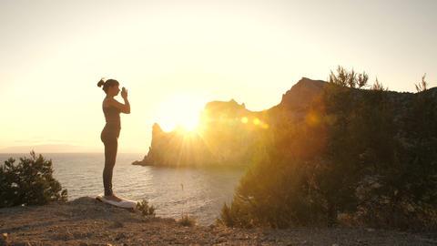 Woman do yoga at sunset near ocean Acción en vivo