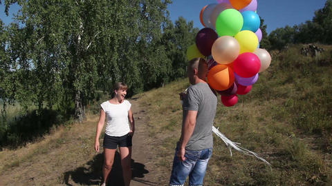 Boy gives a girl with red hearts helium and they go for a walk Footage