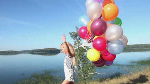 Close-up of a little girl with balloons running on the... Stock Video Footage
