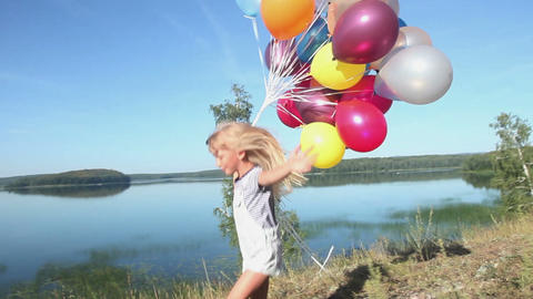 Close-up of a little girl with balloons running on the background of sky and wat Live Action