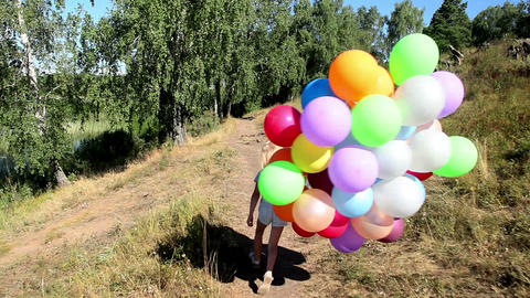 Little girl with balloons running on the path along the lake Footage