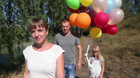 Attractive young woman, her husband and daughter walking in the park during the  Footage