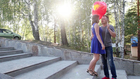 Boy gives a girl with red hearts helium and they go for a walk Live Action
