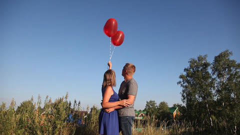 Guy and girl start the sky helium balloons in form of hearts Live Action