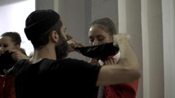 Behind the scenes of the fashion show. The designer wears a mask on a model Live Action