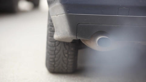 Rear view on car, close up shot of exhaust pipe. Car engine starts, lot of smoke Live Action