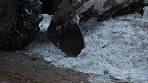 Wheeled loader tractor cleaning road, steel scoop scrape dirty snow Footage