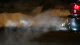 Vehicle exhaust gas, close up side view of smoke curling from car tail pipe Live Action