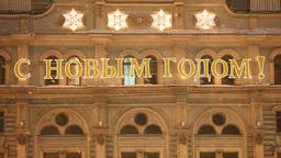 Glowing letters with russian New Year greeting on old building facade Footage