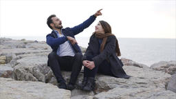 Young couple sitting next to the sea on the stone - Slow Motion Footage