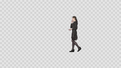 Young woman in black walking and talking by phone. Footage with alpha channel Footage