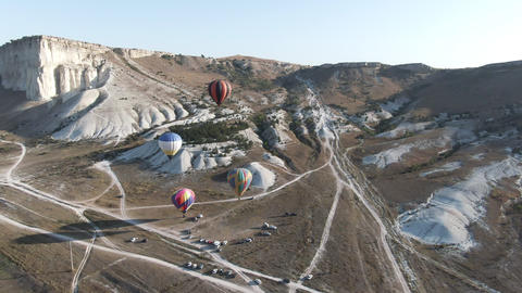 four balloons take off in the sky at dawn against a white rock Crimea White Rock Footage