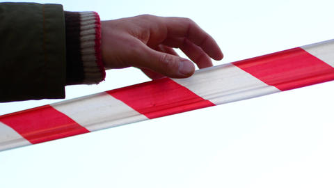 Red and white striped ribbon forbidding passage. The hand removes the tape Live Action