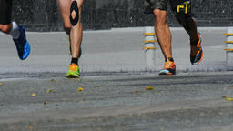 group of young athletes, runners run through a puddle, water sprays under runnin Footage