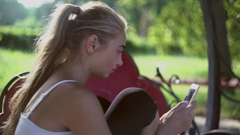 Beautiful blonde girl sitting on a bench in the park, smiling and review mobile  Footage