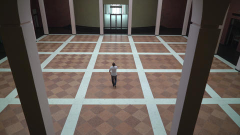 A man walks along in a large room with columns and talking on a cell phone Footage