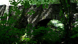 Calm flowing brook, beneath stone foot bridge, in a magical spot with dappled sh Footage