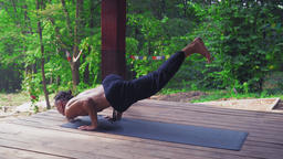 Man performs yoga exercises, lifting one leg and bending the other Footage