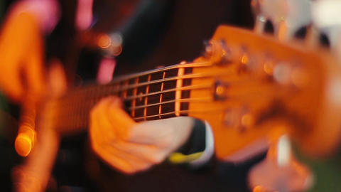 Professional young bass player playing guitar solo. A close up view of the hands Live Action