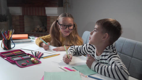 Portrait of two joyful Caucasian children writing in exercise books and talking Footage