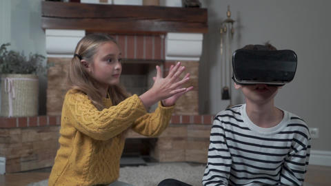 Pretty Caucasian girl waving in front of a little boy wearing VR glasses Footage