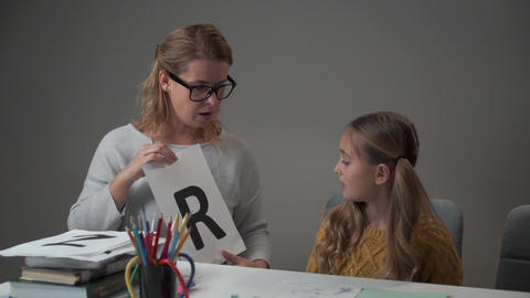 Portrait of a pretty Caucasian girl learning alphabet with her mother. Young Live Action
