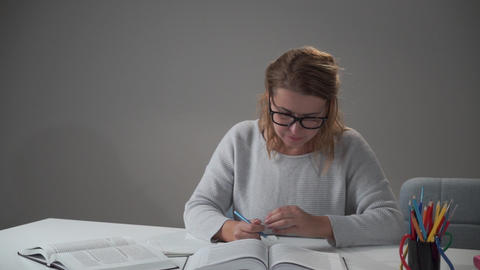 Portrait of a young Caucasian woman in eyeglasses sitting at the table and Live Action