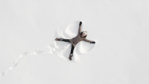 Woman making a snow angel Footage