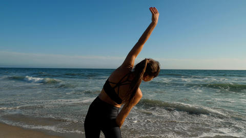 Athletic woman at the beach stretching and relaxing after her workout Footage