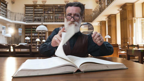 Wise male pensioner with beard in glasses sitting in the library and flipping Live Action
