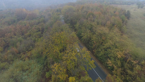 Aerial drone view of silver car driving alone misty road in the mountain. Forest Archivo