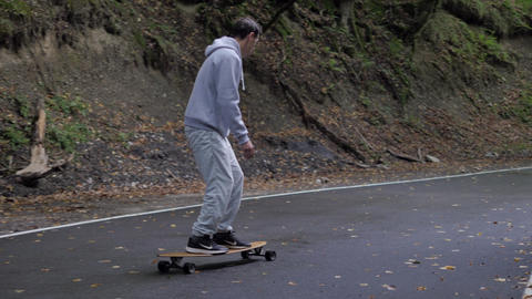 Skateboarder riding carving turns on skateboard on winding road through mountain forest. Close up ビデオ