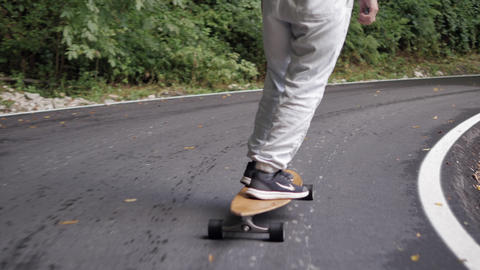 Longboarder legs riding on cruiser longboard on winding road through mountain forest. Close up man ビデオ