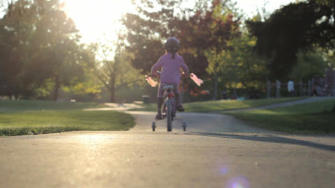 Little Girl Slowly Rides Her Bike To The Playground Footage