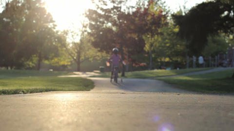 Little Girl Slowly Rides Her Bike To The Playground Stock Video Footage