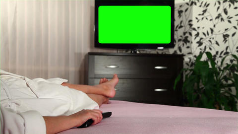 Woman watches green screened TV Stock Video Footage