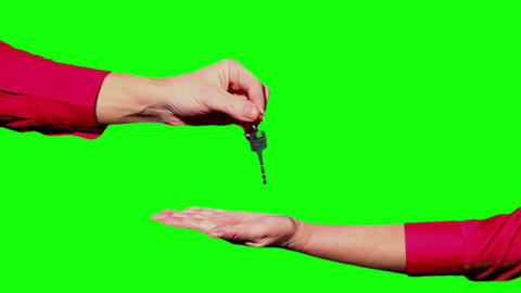 Handing the keys on a green background Stock Video Footage