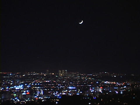 A crescent moon shines over a nighttime city skyline Footage