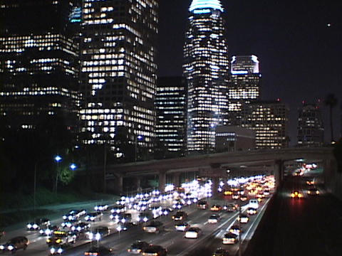Heavy traffic drives through downtown Los Angeles at night Footage