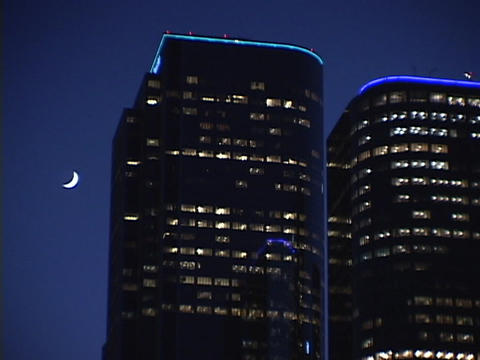 A high rise office building dwarfs a new moon in the night sky Footage