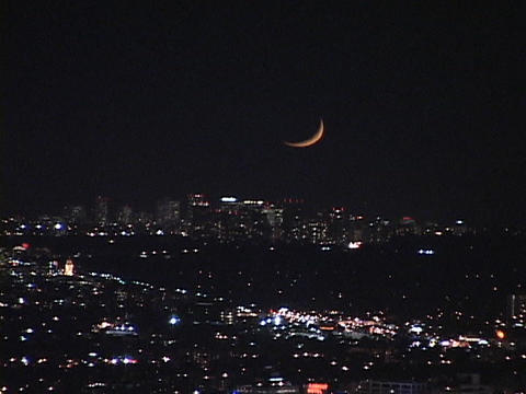 A sliver of moon hangs low in the night sky Stock Video Footage
