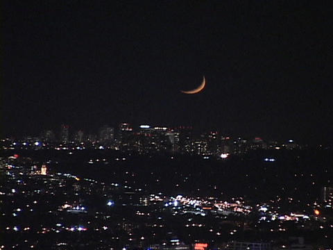A sliver of moon hangs low in the night sky Footage