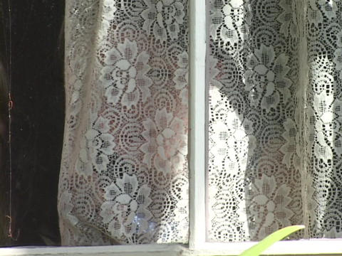 A girl looks through lace window curtains Stock Video Footage