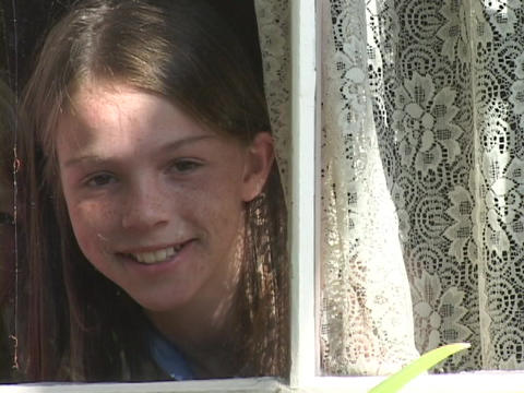 A girl looks through lace window curtains Footage