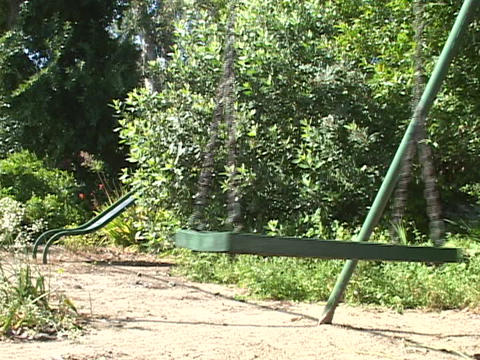 An abandoned swing sways on an empty playground Stock Video Footage