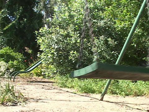 An abandoned swing sways on an empty playground Footage