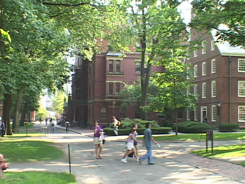 Students walk in front of a Harvard classroom building Stock Video Footage