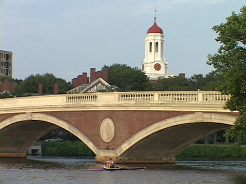 A sculler rows a skiff under a bridge on the Charles River Footage