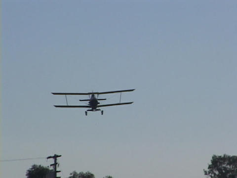 A crop duster flies over farm fields Footage