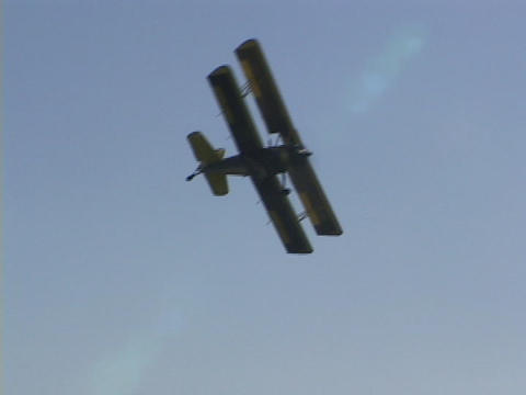 A crop duster flies over farm fields Stock Video Footage